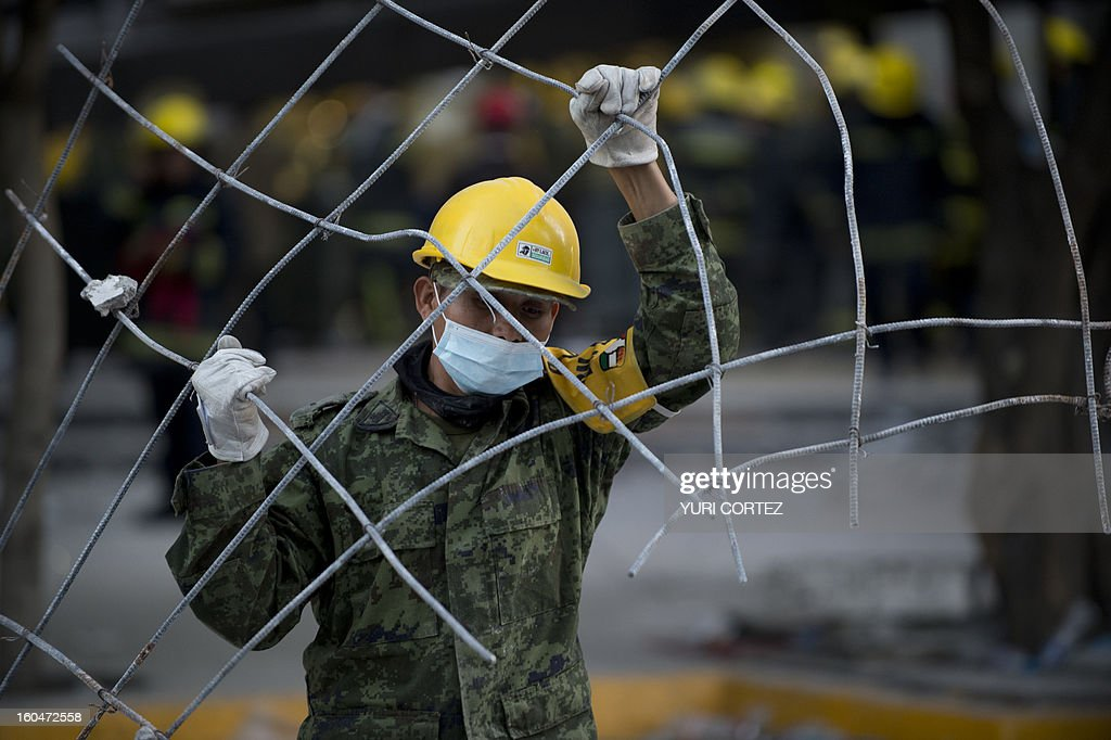 A Mexican soldier removes debris from the headquarters of the state-owned Mexican oil giant Pemex in Mexico City on February 1, 2013, following a blast inside the building. An explosion rocked the skyscraper, leaving up to now 25 dead and 100 injured, as a plume of black smoke billowed from the 54-floor tower, according to official sources. AFP PHOTO/ YURI CORTEZ