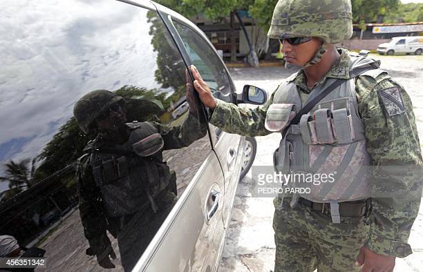 A Mexican soldier searches a van at a checkpoint in Iguala Guerrero State Mexico on September 29 following recent clashes that led to at least six...