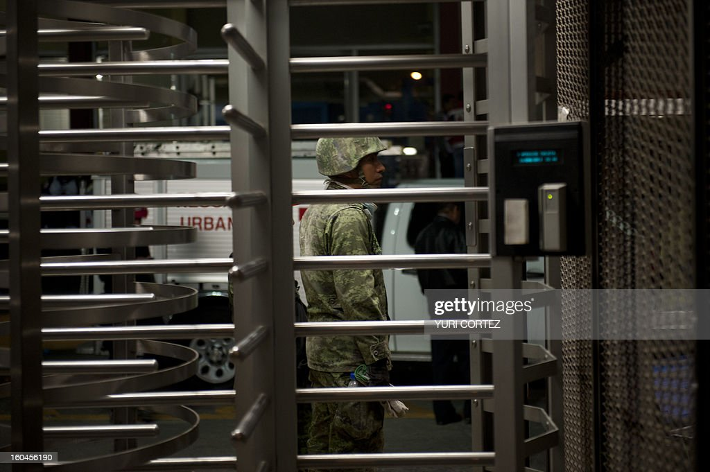 A Mexican soldier stands at the entrance to the headquarters of state-owned Mexican oil giant Pemex in Mexico City on January 31, 2013, following a blast inside the building. An explosion rocked the skyscraper, leaving up to 25 dead and 101 injured, as a plume of black smoke billowed from the 54-floor tower, according to official sources. AFP PHOTO / YURI CORTEZ