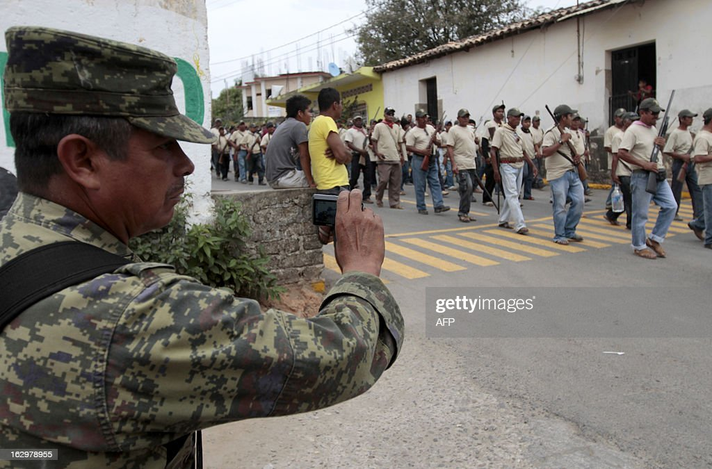 A Mexican soldier takes snapshots as armed residents --community police-- take part in the March for Justice and Dignity, in Ayutla de los Libres, on March 2, 2013, in the southwestern State of Guerrero, Mexico. Hundreds of civilians armed with rifles, pistols and machetes decided to provide security for the communities of Guerrero, creating a vigilante force, saying gangs were committing robberies, kidnappings and murder. Guerrero, home to the Pacific resort town of Acapulco, has been one of the states hardest hit by Mexico's drug violence, which has left more than 70,000 people killed across the country since 2006. AFP PHOTO/Pedro Pardo