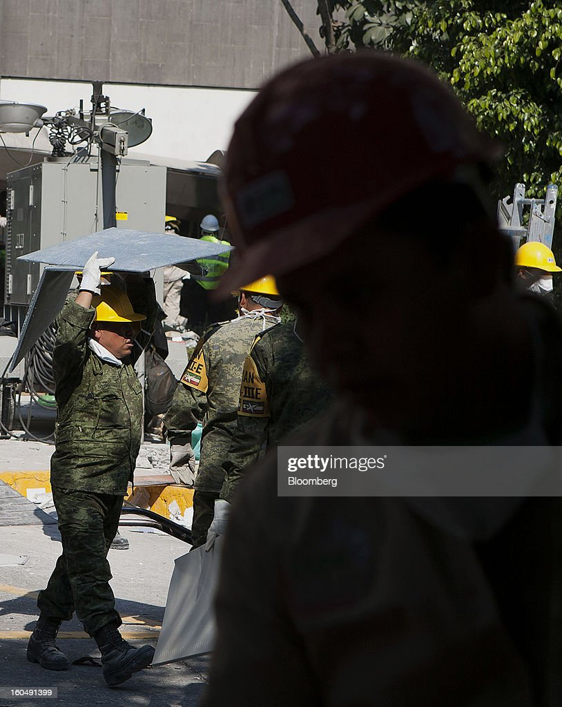 A Mexican soldier wearing the identification of Plan DN-III-E carries debris at the Petroleos Mexicanos (Pemex) administrative building in Mexico City, Mexico, on Friday, Feb. 1, 2013. Pemex is stepping up security at oil production facilities as authorities investigate a blast that killed at least 33 people at the state-owned company's headquarters in Mexico City yesterday. Photographer: Susana Gonzalez/Bloomberg via Getty Images