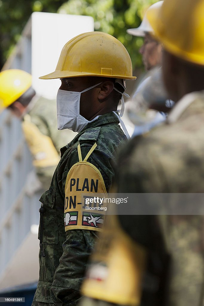 A Mexican soldier wearing the identification of Plan DN-III-E stands amongst debris at the Petroleos Mexicanos (Pemex) administrative building in Mexico City, Mexico, on Friday, Feb. 1, 2013. Pemex is stepping up security at oil production facilities as authorities investigate a blast that killed at least 33 people at the state-owned company's headquarters in Mexico City yesterday. Photographer: Susana Gonzalez/Bloomberg via Getty Images