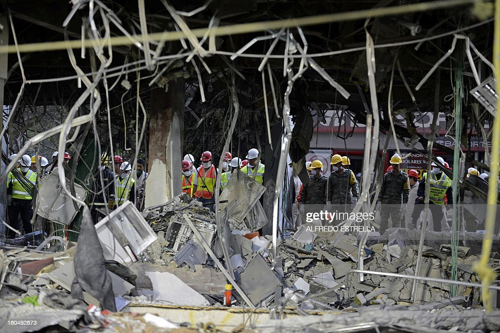 Mexican soldiers and Federal policemen check damages at the building of state-owned Mexican oil giant Pemex, following a blast on the eve, in Mexico City on February 1, 2013. An explosion rocked the skyscraper, leaving up to 32 dead and 121 injured. Hundreds of firefighters, police and soldiers toiled through the night after the blast ripped through an annex of the 54-floor tower leaving concrete, computers and office furniture strewn on the ground. AFP PHOTO/Alredo Estrella