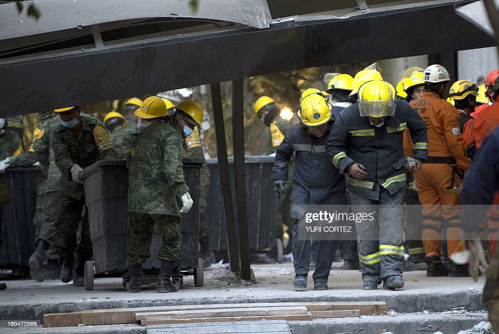 Mexican soldiers and firefighters remove debris from the headquarters of the state-owned Mexican oil giant Pemex in Mexico City on February 1, 2013, following a blast inside the building. An explosion rocked the skyscraper, leaving up to now 25 dead and 100 injured, as a plume of black smoke billowed from the 54-floor tower, according to official sources. AFP PHOTO/ YURI CORTEZ