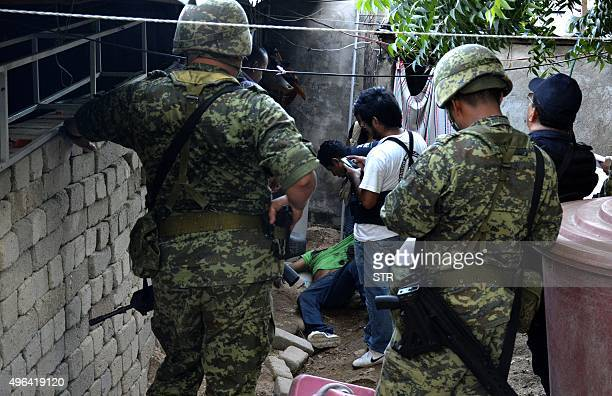 Mexican soldiers and forensic personnel work at a crime scene in Acapulco Guerrero State Mexico on November 8 2015 Acapulco once known as a...