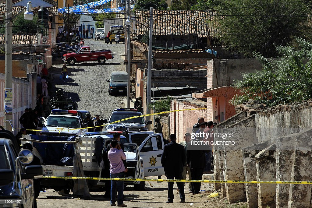 Mexican soldiers and police investigators stand guard at a crime scene in Hostotipaquillo, Jalisco State, Mexico on January 29, 2013. An unidentified armed command killed three people, including the police director of the municipality Hostotipquillo, Lucio Rosales Astorga. AFP PHOTO/Hector Guerrero