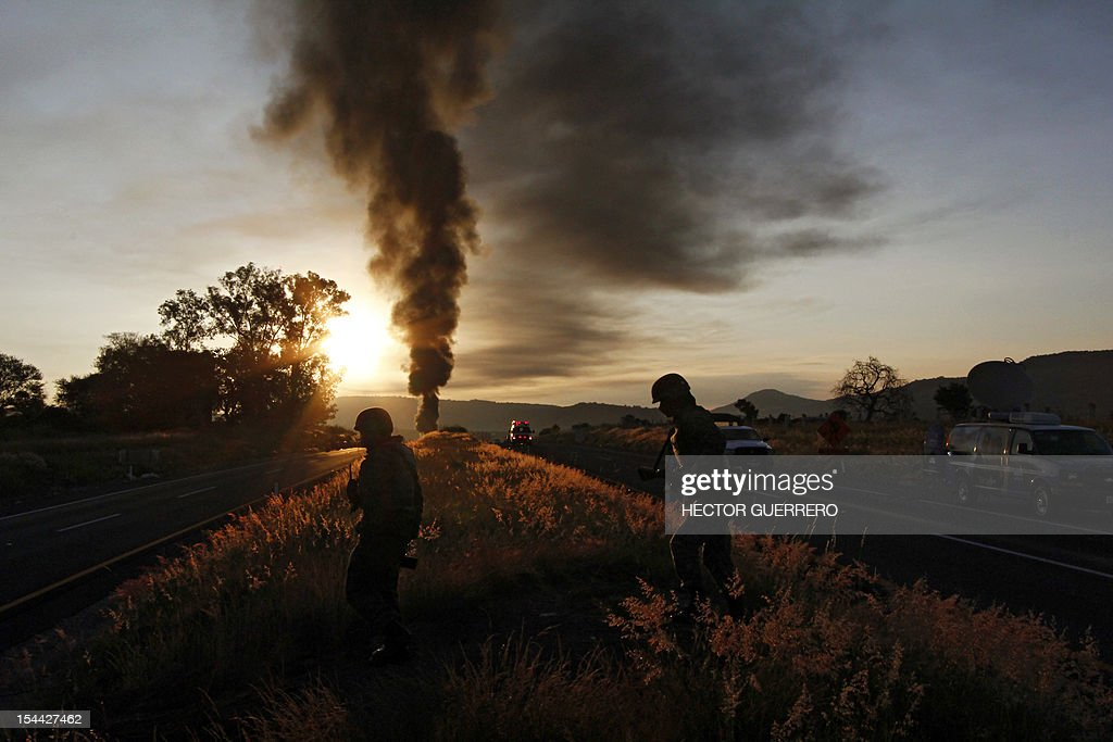 Mexican soldiers are seen backlighted after a gas pipeline explosion in Zapotlanejo, 30 km from Guadalajara city, Jalisco State, Mexico on October19, 2012. A leaking gas pipeline exploded in western Mexico, forcing the evacuation of 2,000 people, and injuring at least three, as crews battled Friday to put out the blaze. The fire broke out Thursday evening in the town of Zapotlanejo near a highway and forced authorities to close the road, said Trinidad Lopez Rivas, head of the emergency services department in Jalisco state. AFP PHOTO/Hector Guerrero