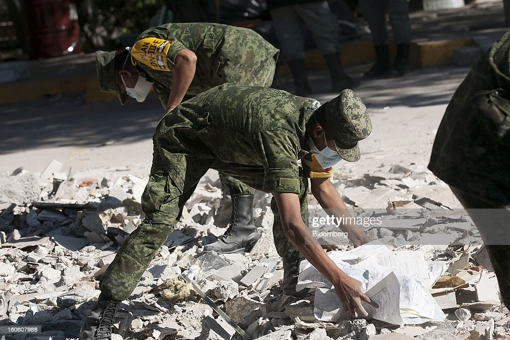 Mexican soldiers clean up debris and recover administrative documents at the Petroleos Mexicanos (Pemex) administrative building in Mexico City, Mexico, on Sunday, Feb. 3, 2013. The search for the cause of a blast that destroyed three floors of a building at Pemex' headquarters and killed at least 34 people entered a fourth day, as investigators toiled ahead of a self-imposed deadline for finding an answer. Photographer: Susana Gonzalez/Bloomberg via Getty Images