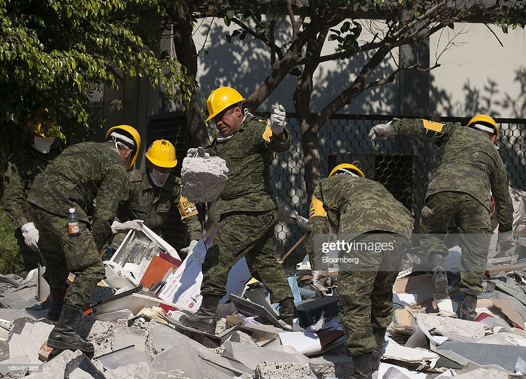 Mexican soldiers clean up debris at the Petroleos Mexicanos (Pemex) administrative building in Mexico City, Mexico, on Friday, Feb. 1, 2013. Pemex is stepping up security at oil production facilities as authorities investigate a blast that killed at least 33 people at the state-owned company's headquarters in Mexico City yesterday. Photographer: Susana Gonzalez/Bloomberg via Getty Images