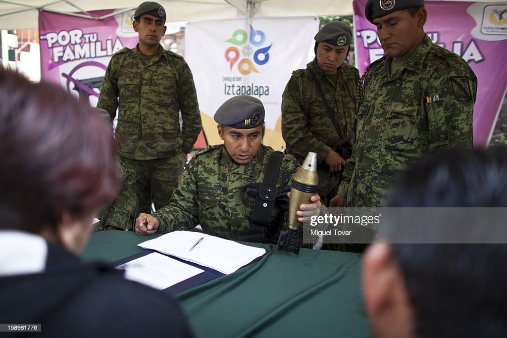 Mexican soldiers examines a grenade after being exchanged by its owner on January 04, 2013 in Mexico City, Mexico. More than a thousand weapons have been changed for a tablet, bicycles or money in a low-income neighborhood in the capital, according to authorities.