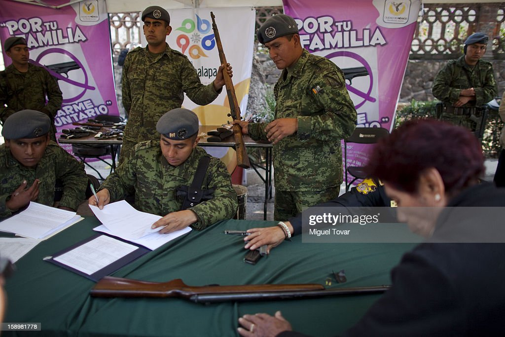 Mexican soldiers examines weapons before being exchanged by its owner on January 04, 2013 in Mexico City, Mexico. More than a thousand weapons have been changed for a tablet, bicycles or money in a low-income neighborhood in the capital, according to authorities.