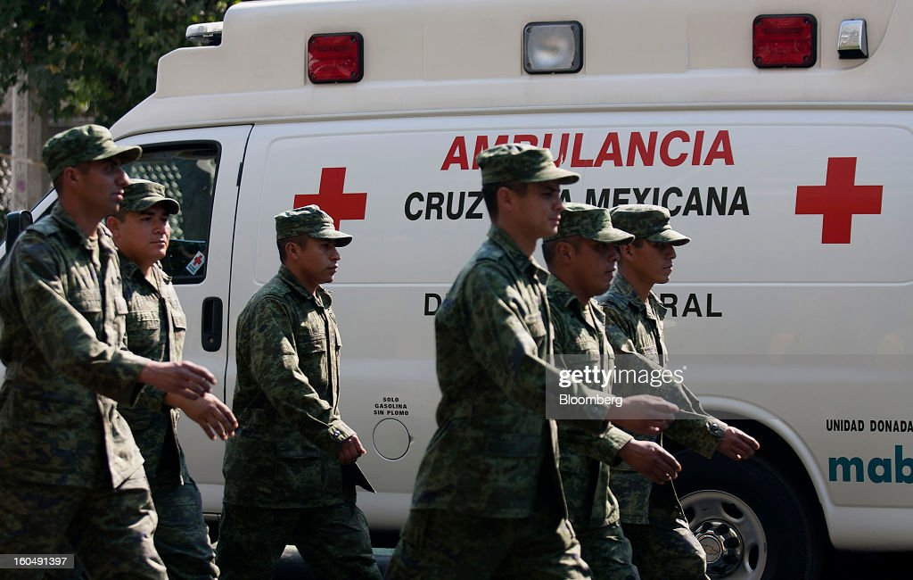 Mexican soldiers march next to a red cross ambulance at the Petroleos Mexicanos (Pemex) administrative building in Mexico City, Mexico, on Friday, Feb. 1, 2013. Pemex is stepping up security at oil production facilities as authorities investigate a blast that killed at least 33 people at the state-owned company's headquarters in Mexico City yesterday. Photographer: Susana Gonzalez/Bloomberg via Getty Images