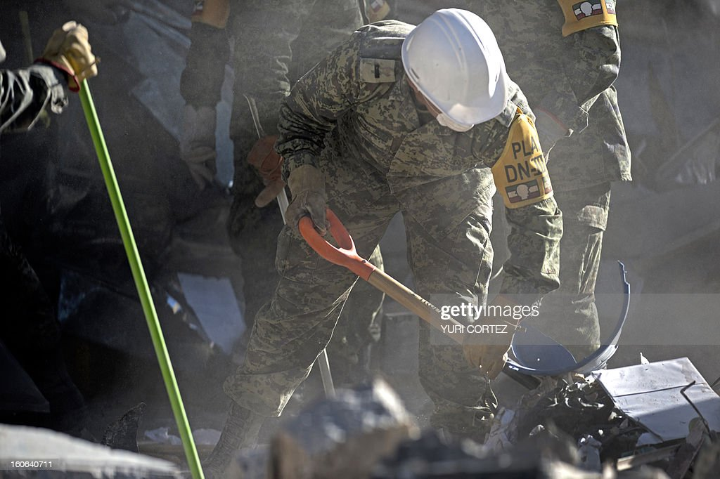 Mexican soldiers remove debris at the building of state-owned Mexican oil giant Pemex, in Mexico City on February 4, 2013. An explosion rocked the skyscraper, last week, leaving up to 36 dead and 121 injured. AFP PHOTO/ YURI CORTEZ