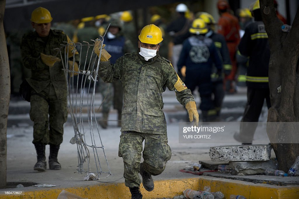 Mexican soldiers remove debris from the headquarters of the state-owned Mexican oil giant Pemex in Mexico City on February 1, 2013, following a blast inside the building. An explosion rocked the skyscraper, leaving up to now 25 dead and 100 injured, as a plume of black smoke billowed from the 54-floor tower, according to official sources.