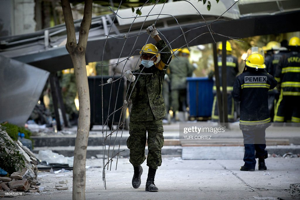 Mexican soldiers remove debris from the rubble at the headquarters of the state-owned Mexican oil giant Pemex in Mexico City on February 1, 2013, following a blast inside the building. An explosion rocked the skyscraper, leaving up to now 25 dead and 100 injured, as a plume of black smoke billowed from the 54-floor tower, according to official sources.