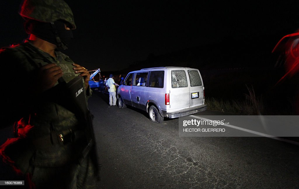 Mexican soldiers stand guard as forensic personnel inspect a destroyed vehicle in Magdalena, Jalisco State, Mexico on 25 January 2013. Five innocent civilians lost their lives during a clash between gangs of organized crime. AFP PHOTO/Hector Guerrero