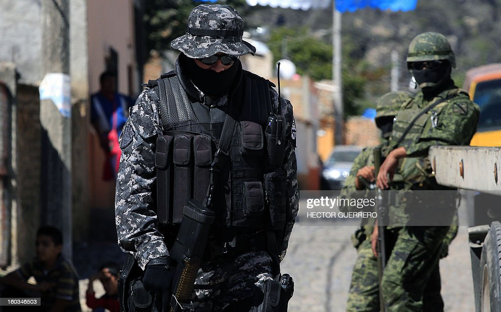 Mexican soldiers stand guard at a crime scene in Hostotipaquillo, Jalisco State, Mexico on January 29, 2013. An unidentified armed command killed three people, including the police director of the municipality Hostotipaquillo, Lucio Rosales Astorga. AFP PHOTO/Hector Guerrero