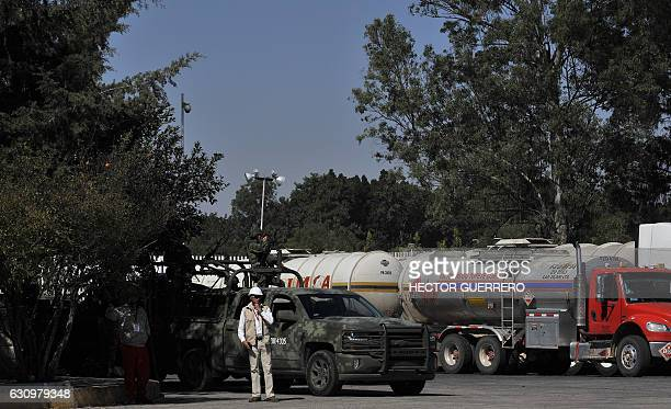 Mexican soldiers stand guard at a Pemex distribution center which is blockaded by truckers protesting the rise in fuel prices in Guadalajara Jalisco...