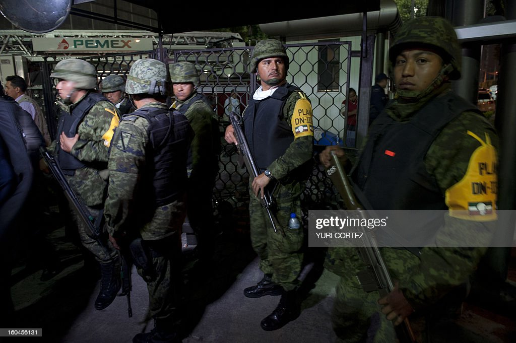 Mexican soldiers stand guard at the headquarters of state-owned Mexican oil giant Pemex in Mexico City on January 31, 2013, following a blast inside the building. An explosion rocked the skyscraper, leaving up to 25 dead and 101 injured, as a plume of black smoke billowed from the 54-floor tower, according to official sources. AFP PHOTO / YURI CORTEZ
