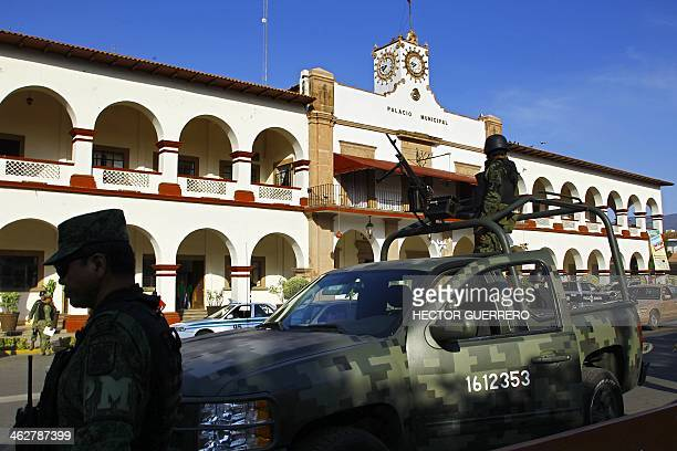 Mexican soldiers stand guard outside the town hall in Apatzingan Michoacan State Mexico on January 15 where government officials hold a meeting with...