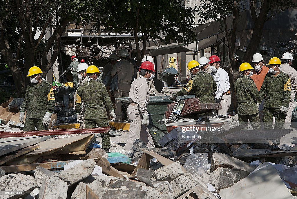 Mexican soldiers wearing the identification of Plan DN-III-E and workers clean up debris at the Petroleos Mexicanos (Pemex) administrative building in Mexico City, Mexico, on Friday, Feb. 1, 2013. Pemex is stepping up security at oil production facilities as authorities investigate a blast that killed at least 33 people at the state-owned company's headquarters in Mexico City yesterday. Photographer: Susana Gonzalez/Bloomberg via Getty Images