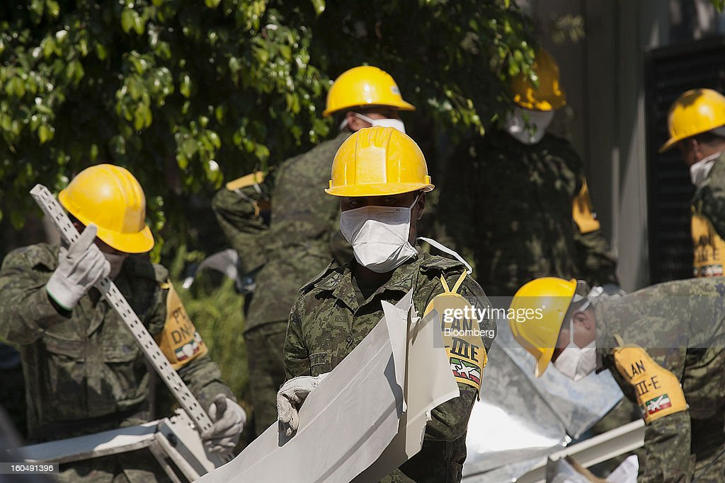 Mexican soldiers wearing the identification of Plan DN-III-E clean up debris at the Petroleos Mexicanos (Pemex) administrative building in Mexico City, Mexico, on Friday, Feb. 1, 2013. Pemex is stepping up security at oil production facilities as authorities investigate a blast that killed at least 33 people at the state-owned company's headquarters in Mexico City yesterday. Photographer: Susana Gonzalez/Bloomberg via Getty Images