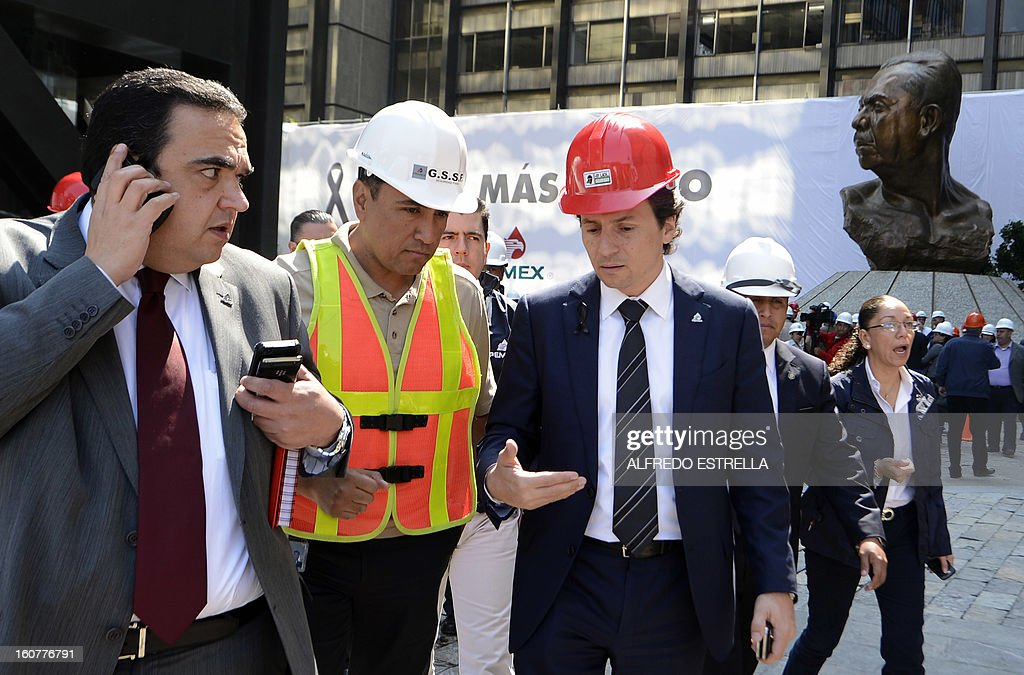 Mexican state-owned oil giant Pemex's Chief Executive Officer, Emilio Lozoya (R), talks with staff members outside the damaged building of the company, after a blast, in Mexico City on February 5, 2013. A gas build-up caused the explosion that rocked the headquarters of Mexico's state-owned oil firm last week, killing 37 people, officials said Monday, ruling out a bomb attack. The explosion also injured morfe than 120 people. AFP PHOTO/Alredo Estrella