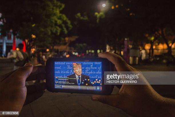 A Mexican student watches on his smartphone the first US presidential debate between Donald Trump and Hillary Clinton on a street in downtown...