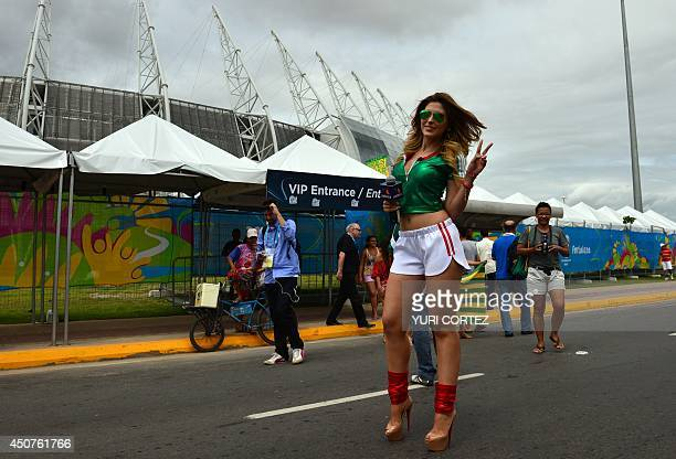 A Mexican television journalist flashes a victory sign as she stands outside The Castelao Stadium in Fortaleza on June 17 ahead of the Group A...