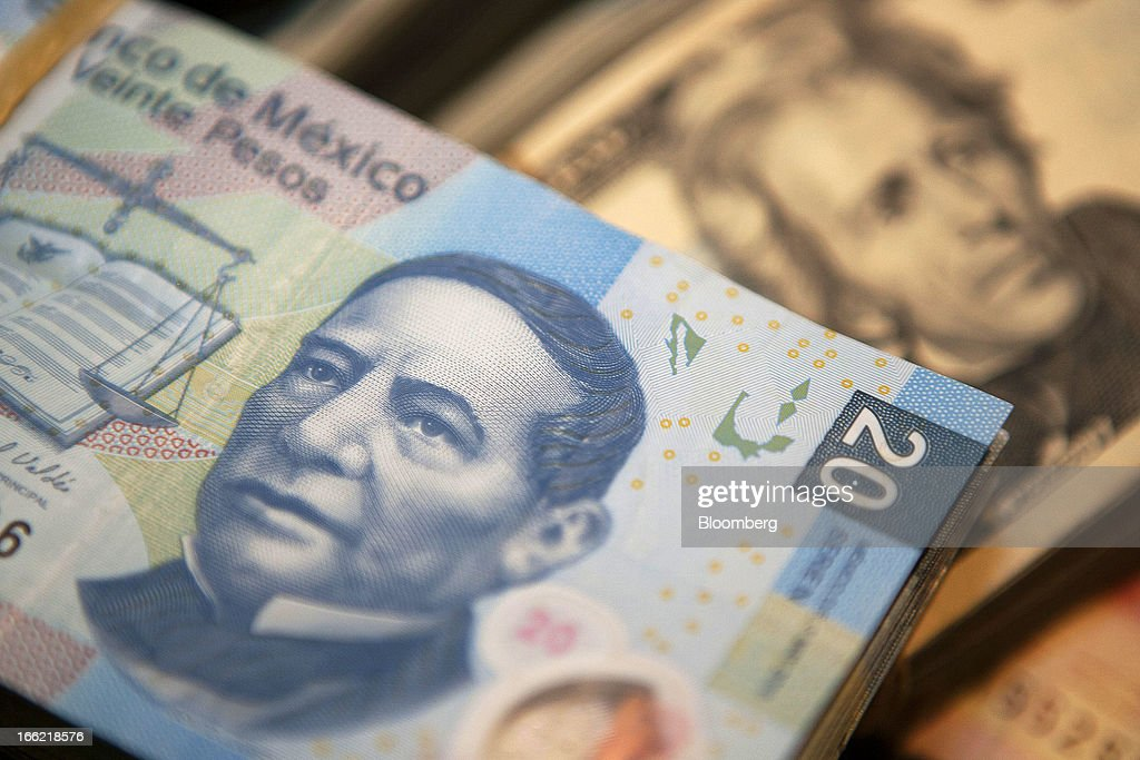 Mexican twenty peso bills and U.S. dollar bills are arranged for a photograph inside a currency exchange in Mexico City, Mexico, on Tuesday April 9, 2013. Mexico's peso rose to the strongest since August 2011 after a report showed faster-than-forecast inflation last month, damping speculation that policy makers will cut interest rates to slow the currency's advance. Photographer: Susana Gonzalez/Bloomberg via Getty Images