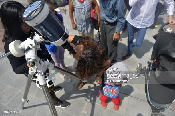 A Mexican woman looks through a telescope at the beginning of the solar eclipse at the esplanade of the Museum of Natural History in Mexico City on...