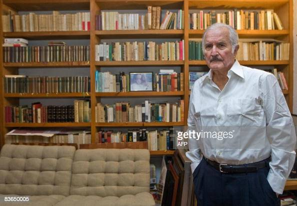 Mexican writer Carlos Fuentes poses in front of his library during a interview with AFP in Mexico City on November 6 2008 Mexico launched on November...