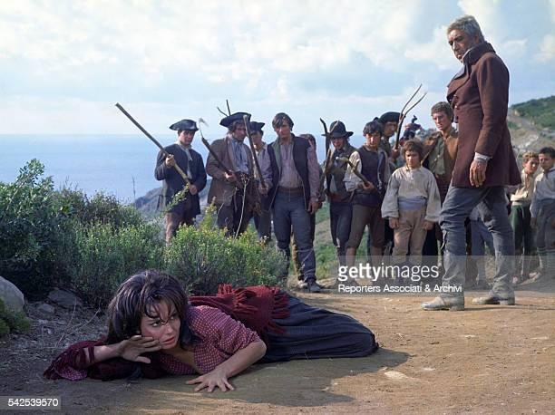 Mexicanborn American actor Anthony Quinn looking at Italian actress Rosanna Schiaffino on the ground in The Rover 1967
