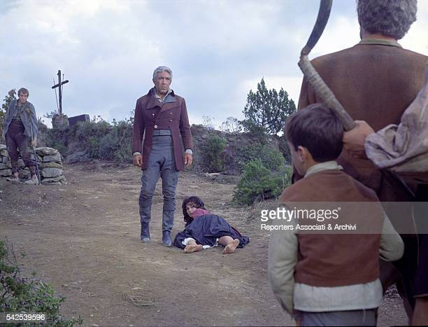Mexicanborn American actor Anthony Quinn next to Italian actress Rosanna Schiaffino on the ground in The Rover 1967