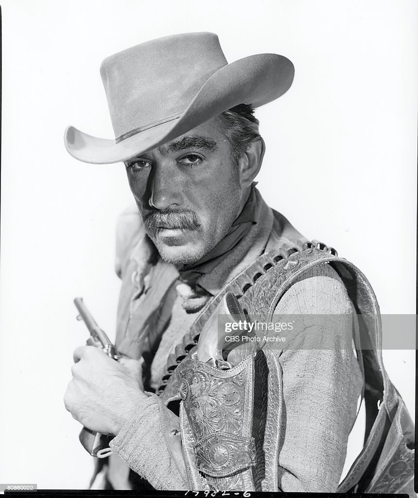 Mexican-born American actor Anthony Quinn (1915 - 2001) poses with a gun in one hand and an ammunition belt with holster over his shoulder on an episode of the 'Schlitz Playhouse of Stars' entitled 'The Long Trail,' October 19, 1954.