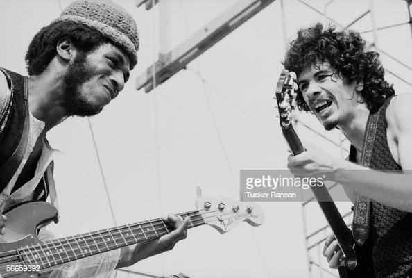 Mexicanborn American musician Carlos Santana and American bassist David Brown perform with the other members of Santana at 'Woodstock' a large rock...