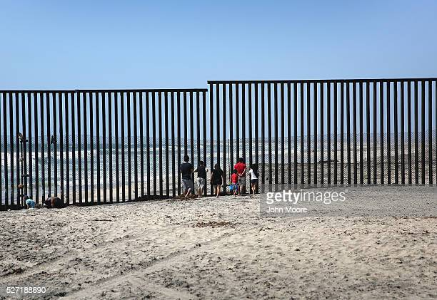 Mexicans stand on the beach while looking through the USMexico border fence into the United States on May 1 2016 in Tijuana Mexico Mexicans on the...