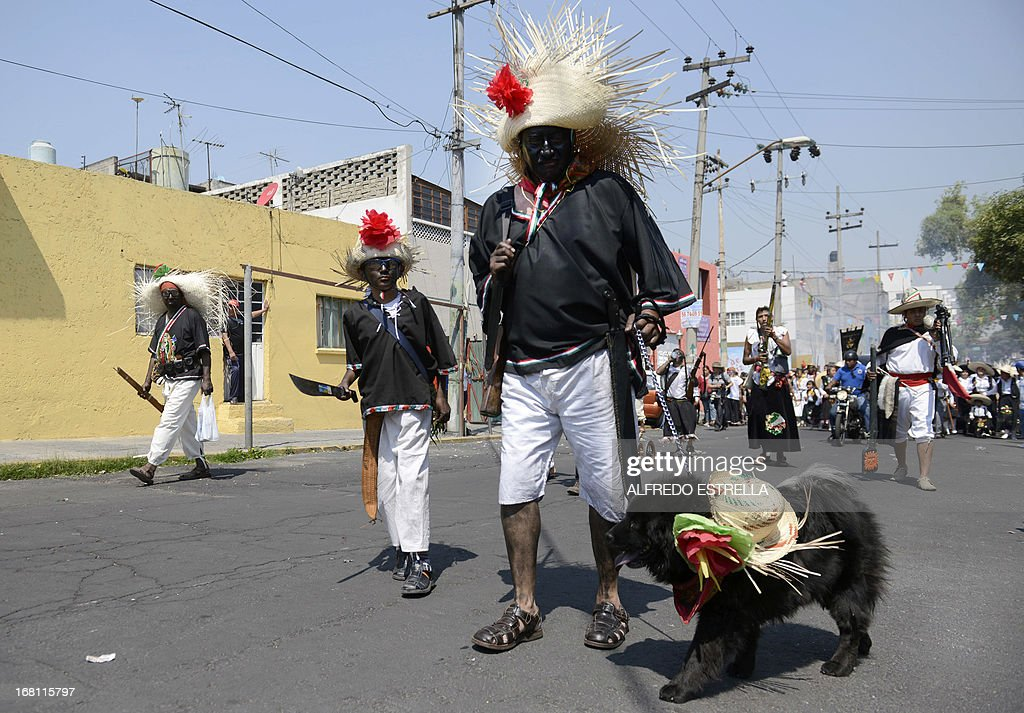 Mexicans wear costumes along the streets of the Penon de los Banos neighborhood in Mexico City, on May 5, 2013, commemorating the anniversary of Mexico's victory over France in the 1862's Battle of Puebla. Although in 1863 France finally took the Mexican capital and installed a five-year regime led by Emperor Maximilian, the Battle of Puebla's importance lies in that it strengthened the Mexican spirit after it prevented Napoleon III from conquering the country in a first attempt. AFP PHOTO/Alfredo Estrella