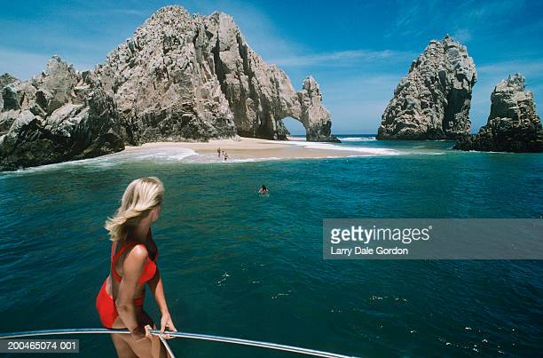 Mexico, Baja, Cabo San Lucas, woman on boat looking at rock formations