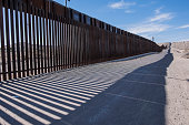 The border fence between New Mexico and Mexico. Strong shadows are cast upon the dirt road on the US side of the border.