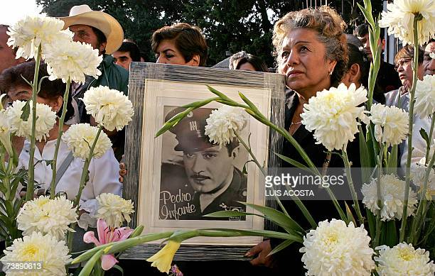 A fan holds a picture of the late Mexican actor and singer Pedro Infante in front of his tomb during the commemoration of the 50th anniversary of his...