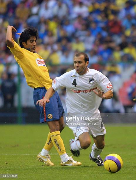 America's Carlos Infante vies for the ball with Santos' Pedro Brazil during their Libertadores Coup football quarterfinals match 16 May 2007 in...