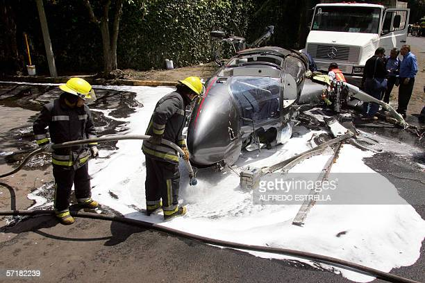Firefighters spray foam over the wreckage of a helicopter carrying eight people on board among them former Real Madrid footballer Argentine Jorge...
