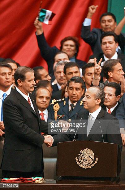 Mexican new President Felipe Calderon shakes hands with outgoing President Vicente Fox before being swornin 01 December 2006 at the Congress in...