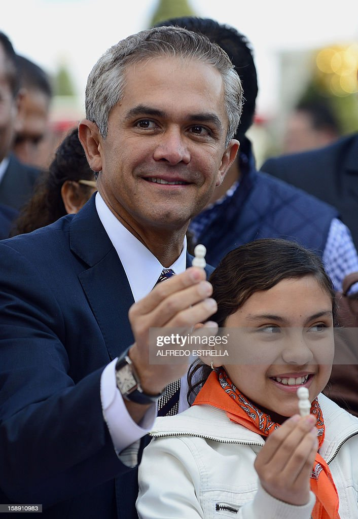 Mexico City's mayor Miguel Mancera (C) and a girl who found a small porcelain baby Jesus inside her pice of the traditional 'Rosca de Reyes' (Mexican Epiphany Bread) --a large ring-shaped bread roll baked for Epiphany-- pose in Mexico City, on January 3, 2012. The 1900-metre circumference 'Rosca de Reyes', weighing 10 metric tons --the world biggest-- was distributed among 200,000 people at Zocalo Square in the Mexican capital. AFP PHOTO/Alfredo ESTRELLA