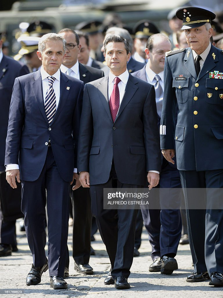 Mexico City's Mayor Miguel Mancera, Mexican President Enrique Pena Nieto and Defence Secretary General Salvador Cienfuegos are pictured during a tour of the exhibition 'Armed Forces, Pride for Serving Mexico' at Zocalo Square in Mexico City, following a ceremony involving the Armed Foreces, on February 15, 2013. AFP PHOTO/Alfredo ESTRELLA