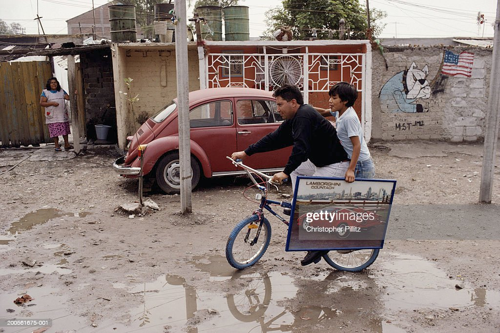 Mexico, Mexico City, man and boy on bicycle in slum : Stock Photo