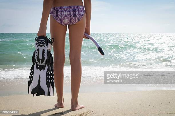 Mexico, Nayarit, teenage girl with snorkel and fins standing in front of the ocean