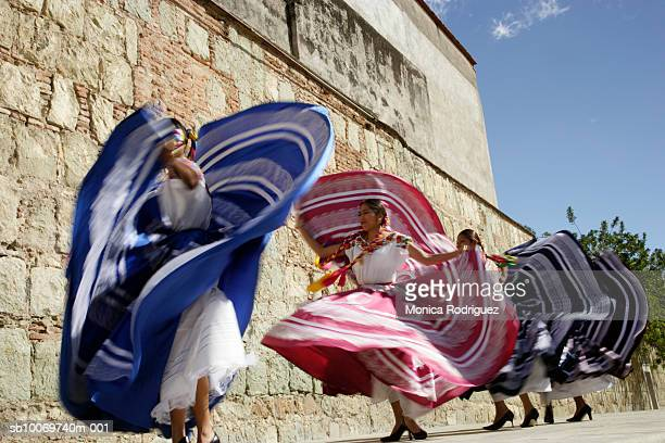 Mexico, Oaxaca, Istmo, four women in traditional dress dancing, blurred motion