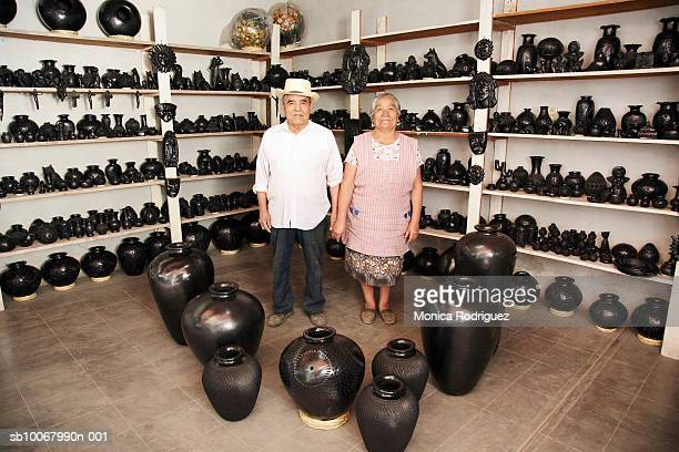 Mexico, Oaxaca, senior couple standing in pottery shop, portrait